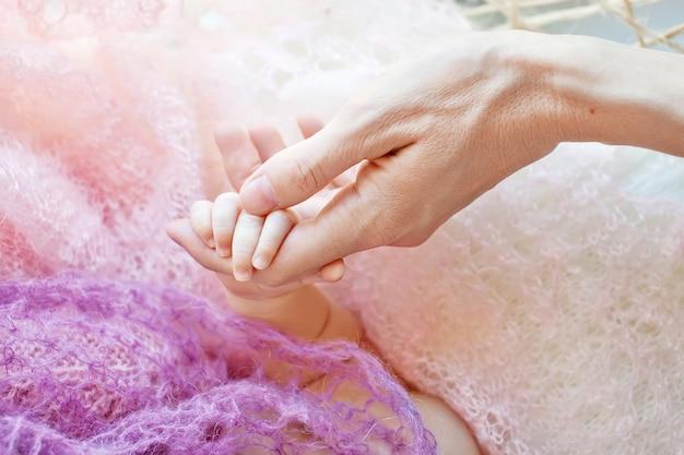 Noworodka ręka w rękę matki. mama i jej dziecko. szczęśliwa rodzina koncepcja. piękny koncepcyjny obraz macierzyństwa