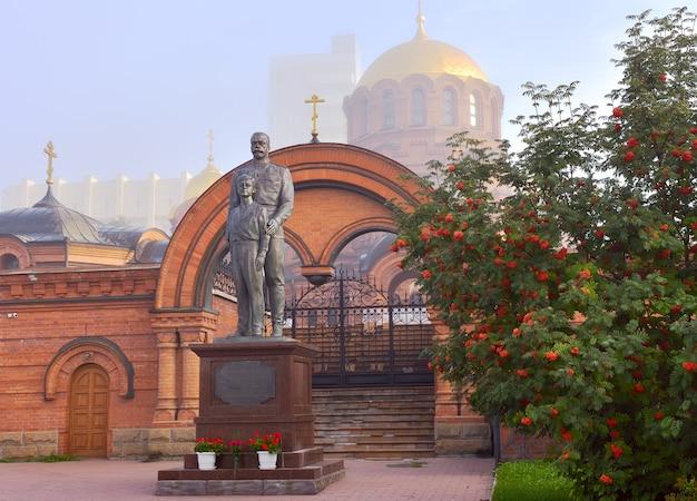Nowosybirsk, syberia, rosja 15.08.2021: posąg ostatniego cesarza rosyjskiego na tle łuku wejściowego, złota kopuła świątyni we mgle