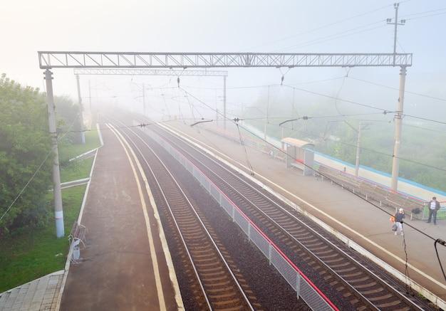 Nowosybirsk, syberia, rosja, 15.08.2021: tory rozpływają się we mgle, opustoszały peron stacji kolejowej prawy ob