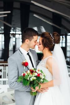 Nowożeńcy całują się w sali restauracyjnej.