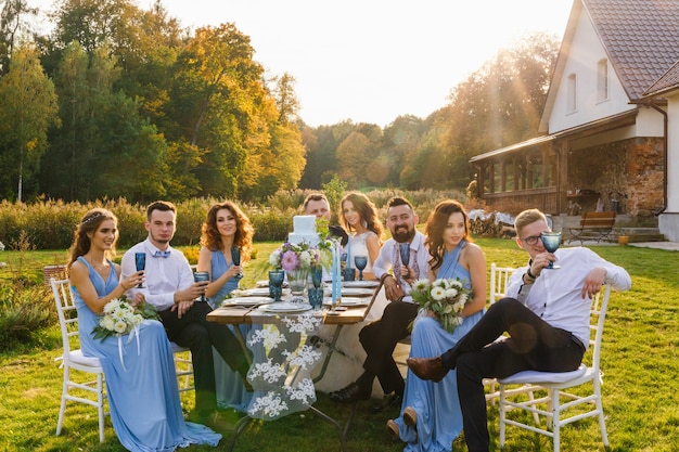 Nowożeńcy i goście bawią się przy stole bankietowym