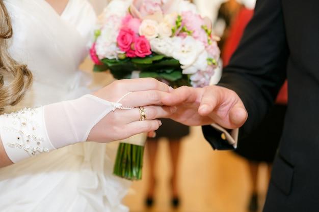 Nowożeńcy młodej pary noszą obrączkę na ślubie