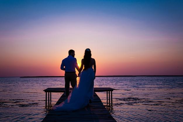 Nowożeńcy na oceanie o zachodzie słońca. tylko zakochana para, która świętowała ślub w sukniach ślubnych, stoi na drewnianym moście na morzu na tle pięknego zachodu słońca.