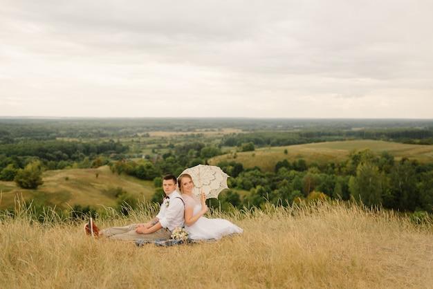 Nowożeńcy na piknik w przyrodzie. narzeczeni po ceremonii ślubnej.
