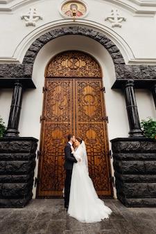 Nowożeńcy obejmują się i stoją na tle kościoła