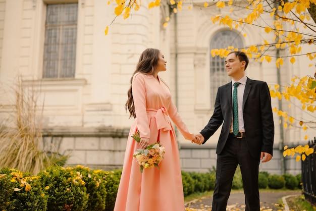 Nowożeńcy oczyszczenie i panna młoda spacery w parku jesień w pobliżu zabytkowej gotyckiej katedry z atmosferą.