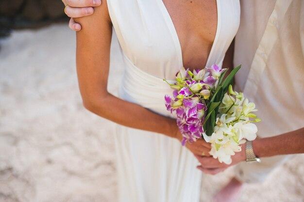 Nowożeńcy pan młody i panna młoda z bukietem ślubnym na plaży nowa komórka społeczeństwa