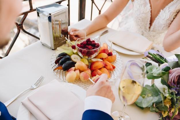 Nowożeńcy państwo młodzi je owoc i pije szampana w dniu ślubu