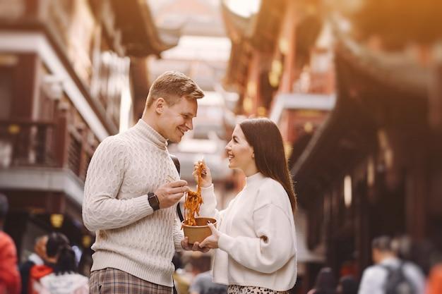 Nowożeńcy para jedzenia makaronu pałeczkami w szanghaju poza rynkiem żywności