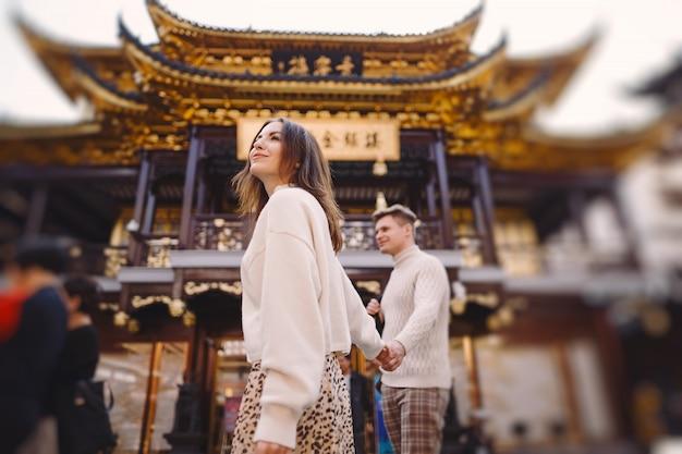 Nowożeńcy para pokazuje sympatię i trzyma ręki w szanghaj blisko yuyuan podczas gdy odwiedzający chiny