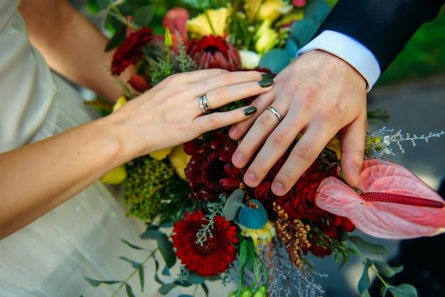 Nowożeńcy para trzymając się za ręce i wyświetlanie obrączki