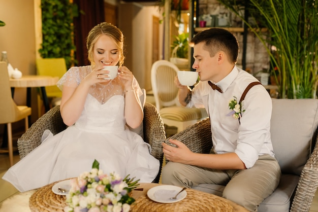 Nowożeńcy piją kawę w przytulnym wnętrzu. państwo młodzi odpoczywają przed ceremonią ślubną.