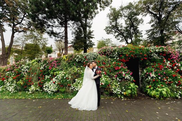 Nowożeńcy pozują w parku wokół nich piękny kwietnik