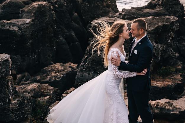 Nowożeńcy przytulają się i uśmiechają na tle dużych kamieni