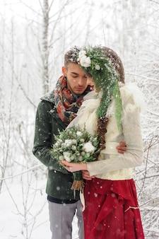Nowożeńcy przytulają się w zimowym lesie. para zakochanych. zimowa ceremonia ślubna.