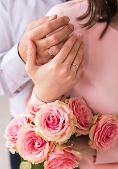 Nowożeńcy ręce z pierścieniami. bukiet ślubny na tle rąk pary młodej ze złotym pierścieniem