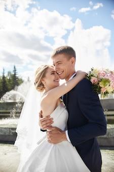 Nowożeńcy spacerują na łonie natury w parku po ceremonii zaślubin. pocałunek i uścisk od mężczyzny i kobiety. pan młody trzyma swoją narzeczoną