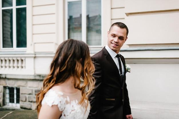 Nowożeńcy spacerują w pobliżu odrestaurowanej architektury, starego budynku, starego domu na zewnątrz, zabytkowego pałacu na zewnątrz.