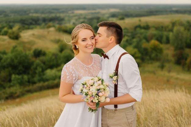 Nowożeńcy stoją na tle pięknego krajobrazu z parasolem. pan młody całuje piękną narzeczoną w policzek