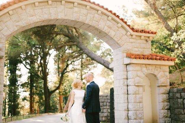 Nowożeńcy stoją przed kamienną bramą z pomarańczowymi płytkami w zielonym parku trzymając się za ręce