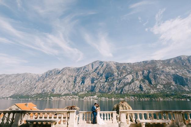 Nowożeńcy stoją w objęciach w pobliżu starożytnego ogrodzenia na brzegu, na tle gór
