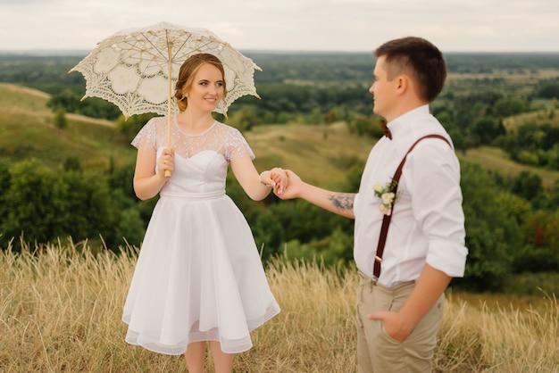 Nowożeńcy stoją z parasolem na tle pięknego krajobrazu