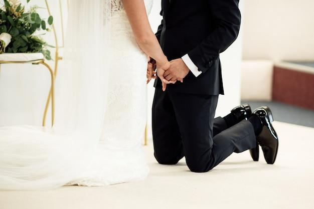 Nowożeńcy stojąc na kolanach, trzymając się za ręce i zamykając oczy.