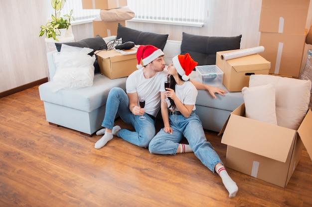 Nowożeńcy świętują boże narodzenie lub nowy rok w swoim nowym mieszkaniu. młody szczęśliwy mężczyzna i kobieta pije wino, świętuje przeprowadzkę do nowego domu i siedzi wśród pudeł.