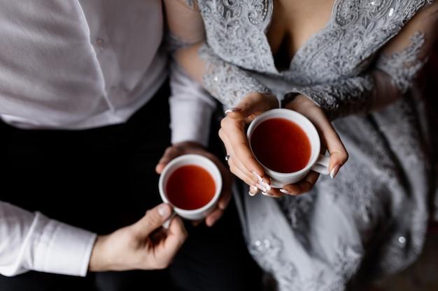 Nowożeńcy trzymają ciepłą herbatę