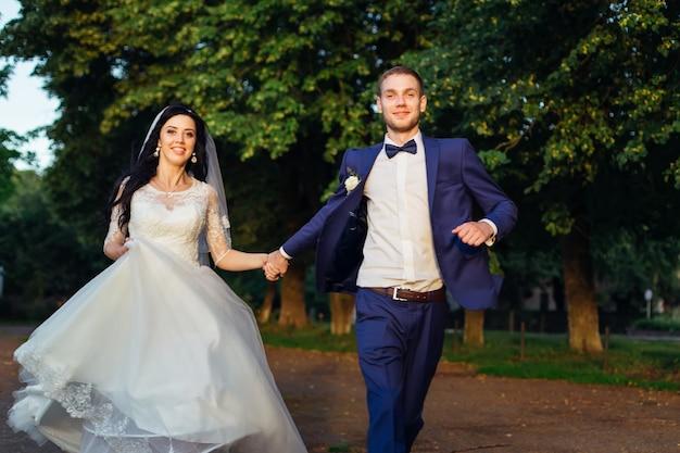 Nowożeńcy trzymają się za ręce i biegają. panna młoda i pan młody w parku.
