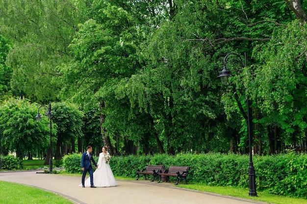 Nowożeńcy trzymają się za ręce i spacerują po pięknym parku. panna młoda trzyma bukiet ślubny.