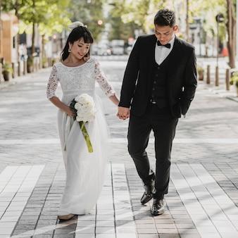 Nowożeńcy trzymają się za ręce idąc ulicą