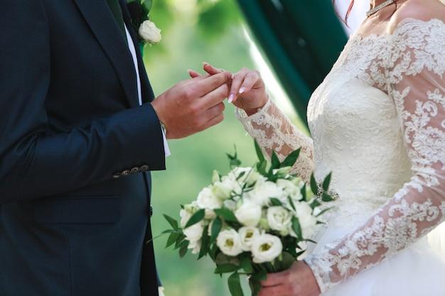 Nowożeńcy trzymają się za ręce na ceremonii ślubnej na świeżym powietrzu