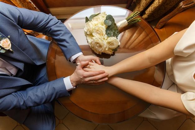 Nowożeńcy, trzymając się za ręce w pobliżu bukietu ślubnego
