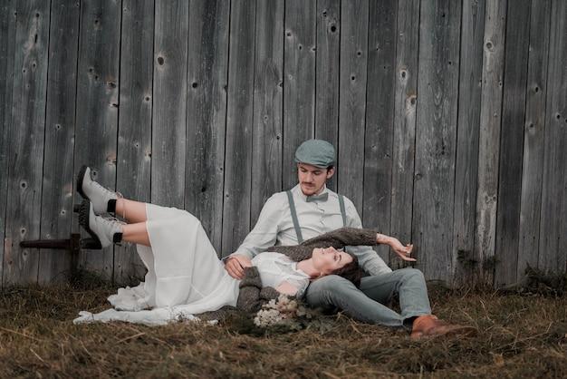 Nowożeńcy ubrani w stylu vintage w pobliżu szarej drewnianej ścianie