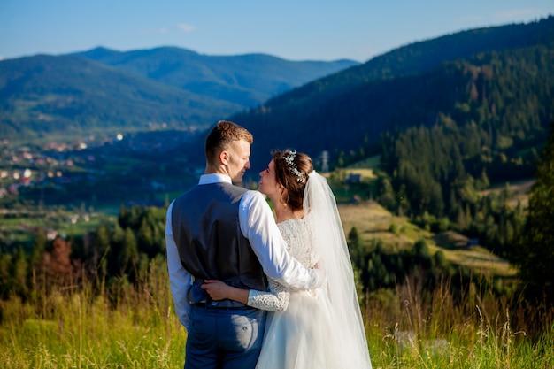 Nowożeńcy uśmiechają się i przytulają do siebie na łące na szczycie góry. ślubny spacer po lesie w górach, delikatne emocje pary, zdjęcie na walentynki