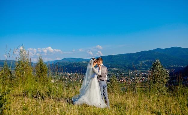 Nowożeńcy uśmiechają się i przytulają na łące na szczycie góry.