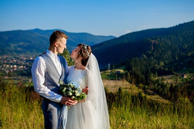 Nowożeńcy uśmiechają się i przytulają na łące na szczycie góry
