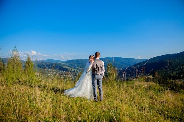 Nowożeńcy uśmiechają się i przytulają się na łące na szczycie góry. weselny spacer po lesie w górach, delikatne emocje pary
