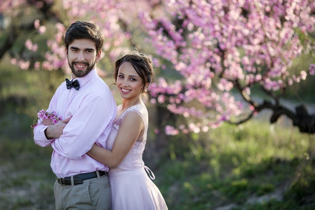 Nowożeńcy w miłości stoją na naturze, na tle drewnianych kołków, przy słonecznej pogodzie. stylowy pan młody obejmuje piękną pannę młodą w koronkowej sukience w zielonym ogrodzie.