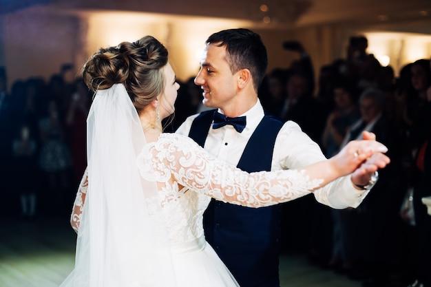 Nowożeńcy w odświętnych strojach tańczą pierwszy taniec w sali restauracji
