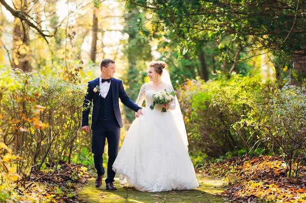 Nowożeńcy w parku trzymają się za ręce i patrzą na siebie