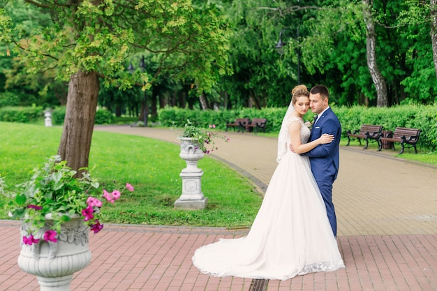 Nowożeńcy w świątecznym stroju przytuleni w pięknym parku.