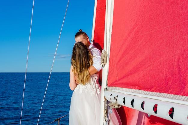 Nowożeńcy w weselnej wycieczce nad morze na jachcie żaglowym