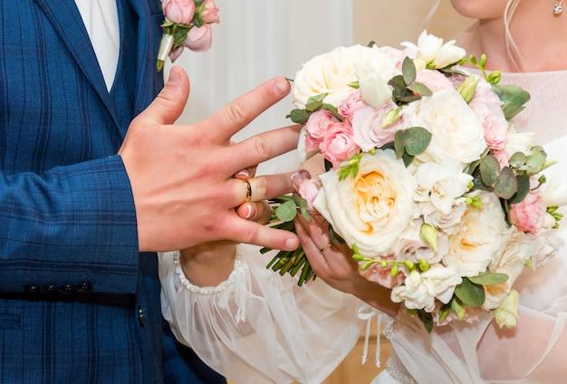 Nowożeńcy wymieniają obrączki, pan młody zakłada obrączkę panny młodej w urzędzie stanu cywilnego.