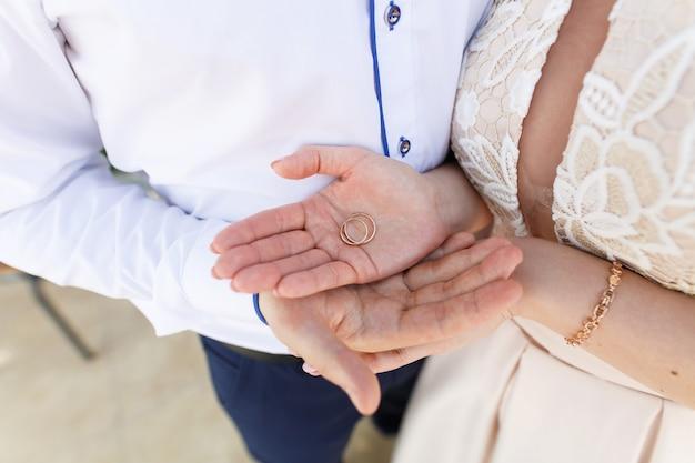 Nowożeńcy z dwiema złotymi obrączkami z bliska. para ślub trzyma swoje pierścienie. ślub. ceremonia zaślubin