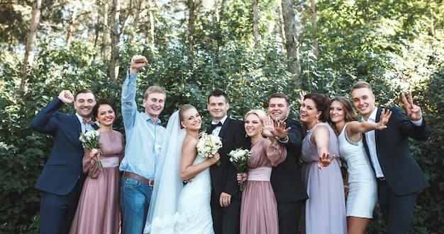 Nowożeńcy z przyjaciółmi stwarzających w parku