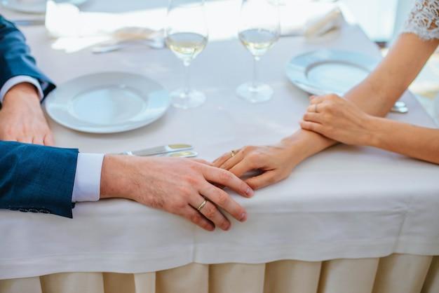 Nowożeńcy zbliżenie trzymają się za rękę przy stole w restauracji z dwoma kieliszkami wina