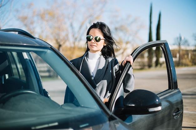 Nowożytna bizneswoman pozycja obok samochodu