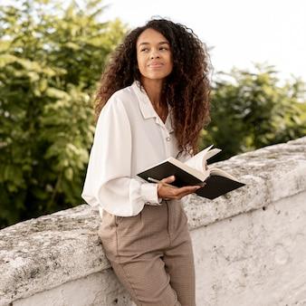 Nowożytna kobieta czyta książkę outdoors